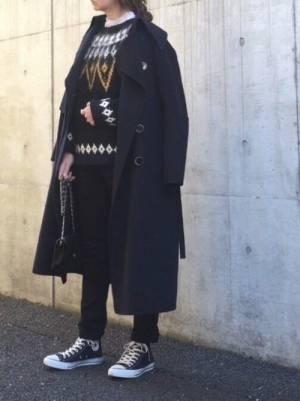 ニットにフリルのブラウスを合わせて黒いパンツを履いてトレンチコートを羽織った女性