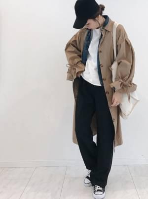デニムジャケットにトレンチコートを合わせて黒いワイドパンツを履いた女性