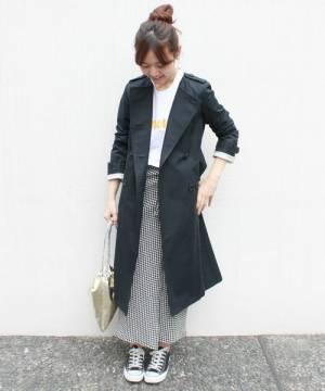 白トップスにギンガムチェックのスカートを合わせて黒いトレンチコートを着た女性