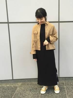 ベージュのジャケットに黒ワンピースを合わせる女性