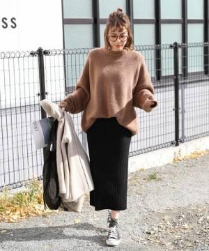 ブラウンニットに黒いニットスカートを履いた女性