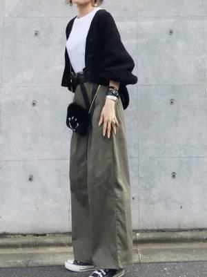白のトップス、カーキのワイドパンツに黒のカーディガンを着た女性