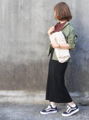 ブラウンのトップス、黒のタイトスカートにカーキのミリタリージャケットを着た女性