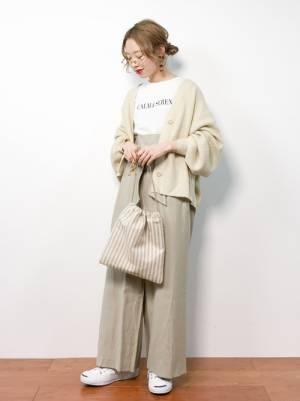 白のロゴT、ベージュのワイドパンツに白のカーディガンを着た女性