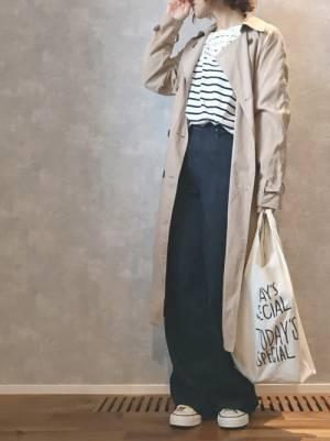 ボーダートップス、デニムワイドパンツにベージュのトレンチコートを着た女性