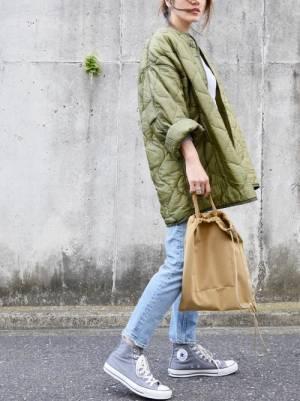 白のトップス、デニムパンツにカーキのキルティングジャケットを着た女性