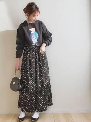 黒のロゴスウェットに黒のドット柄パンツを履いた女性