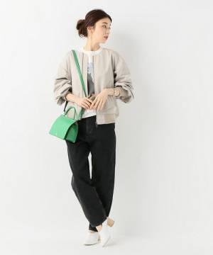 白のグラフィックT、黒のデニムパンツにグレージュのブルゾンを着た女性