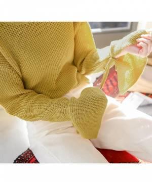 袖フリルニットに白パンツを履いた女性