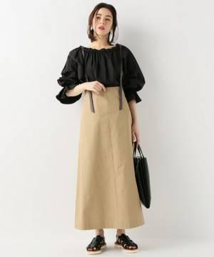 黒トップスにベージュチノスカートを履いた女性