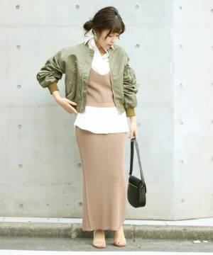 ニットビスチェとスカートにカーキブルゾンを着た女性