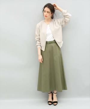 カーキスカートにベージュブルゾンを着た女性