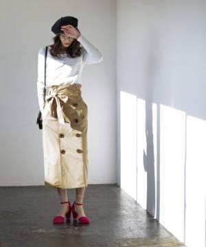 白トップスにベージュトレンチスカートを履いた女性