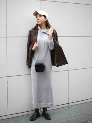 パーカーワンピースとテーラードジャケットを着た女性