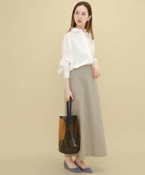 白いブラウスにベージュのスカートを合わせてクリアバッグを持った女性