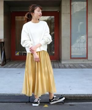 白いスウェットに黄色のスカートを合わせて黒いスニーカーを履いた女性