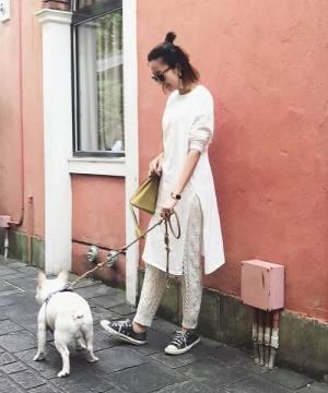 白いワンピにニットパンツを合わせて黒いスニーカーを履いた女性