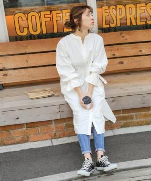 白いシャツワンピにデニムを合わせて黒いスニーカーを履いた女性
