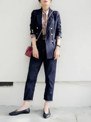 ストライプシャツにテーラードジャケットを合わせてデニムパンツを履いた女性