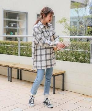 チェックシャツにデニムを合わせてスニーカーを履いた女性
