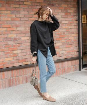 黒いトップスにデニムを合わせてベージュのローファーを履いた女性