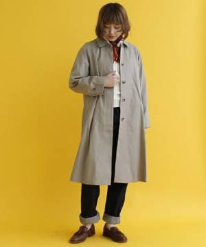 白いトップスにデニムを合わせてステンカラーコートを着た女性