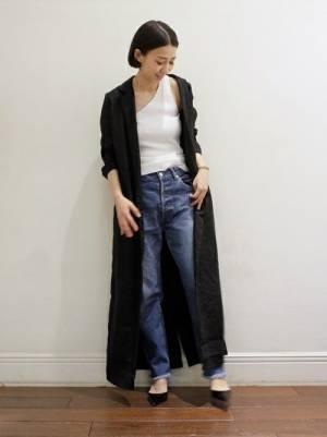 白いタンクトップにデニムを合わせて黒にロングカーデを着た女性