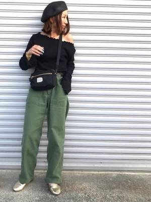黒いニットにカーキのパンツを合わせてゴールドのバレエシューズを履いた女性