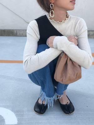 白いリブニットに黒いベストを合わせてデニムを履いた女性