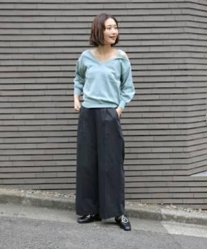 ブルーのニットにワイドパンツを合わせて黒いローファーを履いた女性