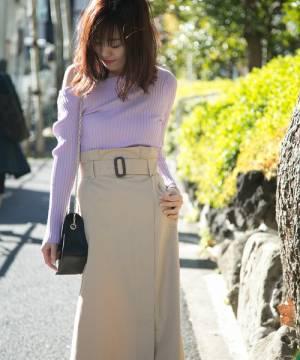 ピンクのワンショルダーニットにベージュスカートを履いた女性