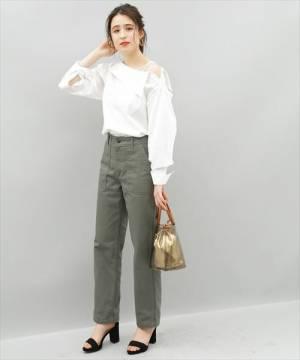 白ワンショルダーシャツにパンツを履いた女性