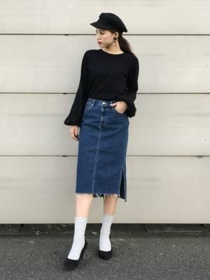 黒いトップスにデニムスカートを合わせてパンプスを履いた女性