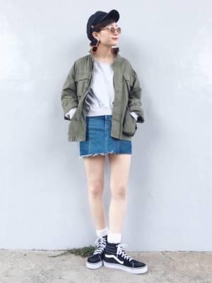 ミリタリージャケットにデニムスカートを合わせて黒いスニーカーを履いた女性