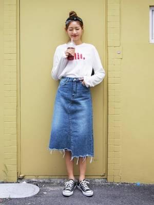 白いトップスにデニムスカートを合わせて黒いスニーカーを履いた女性