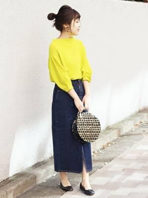 黄色トップスにデニムスカートを合わせた女性