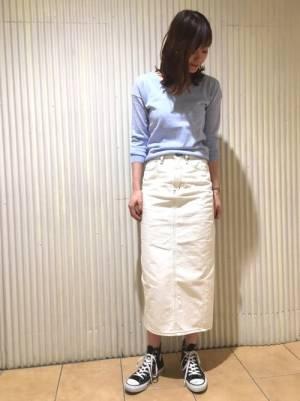 ブルーのトップスに白いデニムスカートを合わせた女性