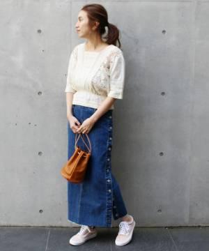 白いトップスにデニムスカートを合わせてスニーカーを履いた女性