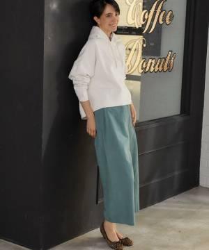白のパーカーにグリーンのワイドパンツを履いた女性