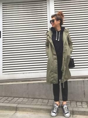 黒のパーカー、黒のテーパードパンツにカーキのモッズコートを着た女性
