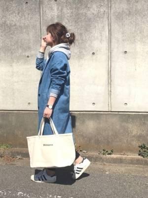 グレーのパーカー、スキニーパンツにデニムコートを着た女性