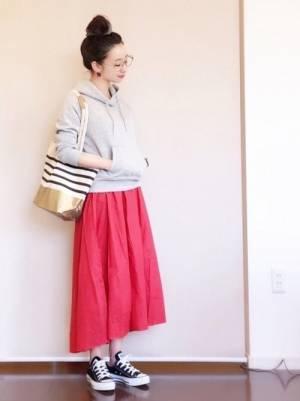 グレーのパーカーに赤のフレアスカートを履いた女性