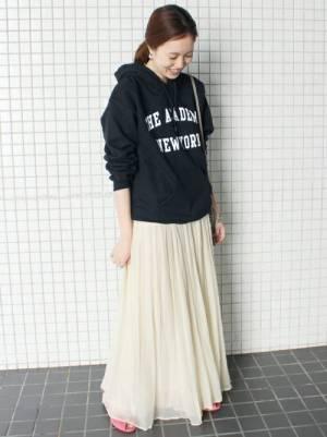 黒のロゴパーカーに白のギャザースカートを履いた女性