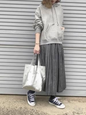 グレーのパーカーにグレーのプリーツスカートを履いた女性