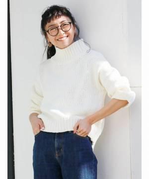 ハイネック白ニットにデニムパンツを履いた女性