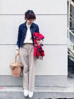 白ニットにベージュパンツ、デニムジャケットを羽織り、赤のチェックマフラーとかごバッグを持った女性