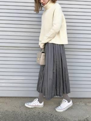 白ニットにグレーのプリーツスカート、グレータイツに白スニーカーを合わせたコーデ