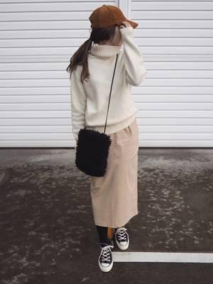 白ニットにベージュのタイトスカート、キャメル系のコーデュロイキャップを被った女性