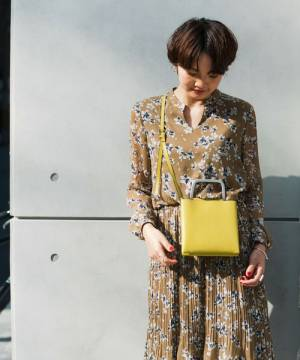 花柄ワンピに黄色のミニショルダーバッグを持った女性