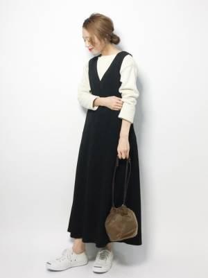 白いトップスにジャンパースカートを合わせてブラウンの巾着バッグを持った女性